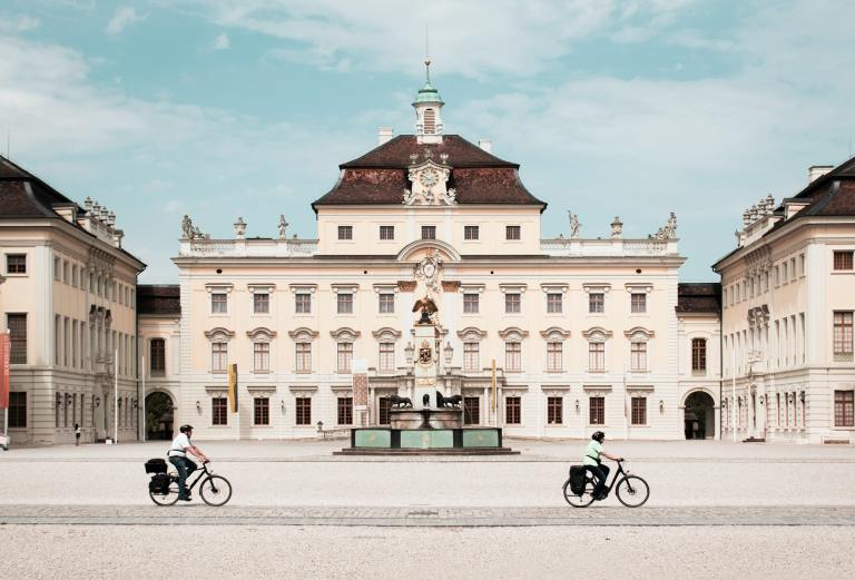 Two people exploring a German city by bike. This is a great way to make travel sustainable.