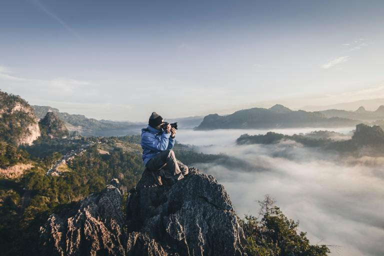 Photographer in Thailand perched on mountain summit.