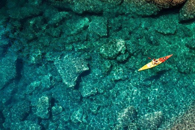 Aerial shot of a person sea kayaking over crystal clear waters.