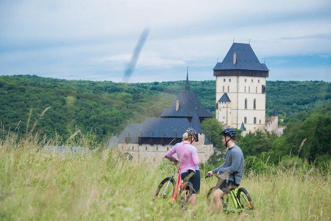 Two tourists on bikes in a field near Karlstejn Castle.
