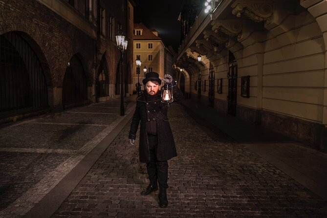Tour guide holding a lantern on a dark street in Prague, ready to lead a ghost walking tour.