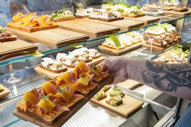 A tray of food being removed from a glass display case at a deli.