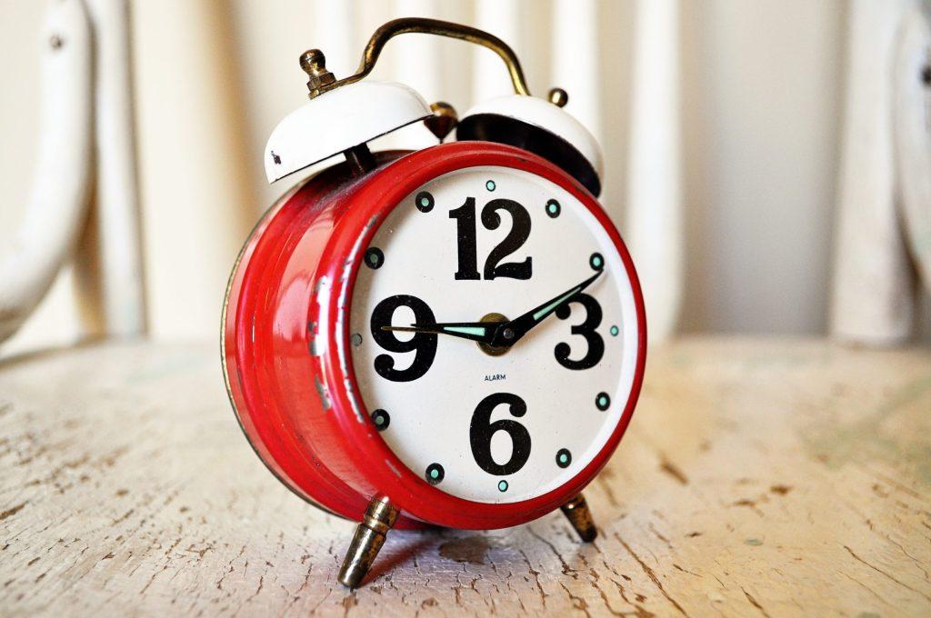 Travailler de chez soi et gestion du temps image d'un réveil rouge