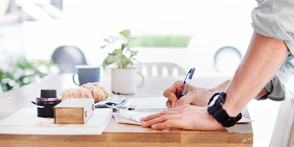 Image d'un homme écrivant sur une table