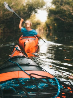 A woman paddles a kayak through a narrow channel bordered on each side by dense foliage.