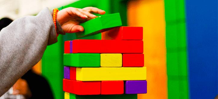 Mão de criança montando torre de brinquedo