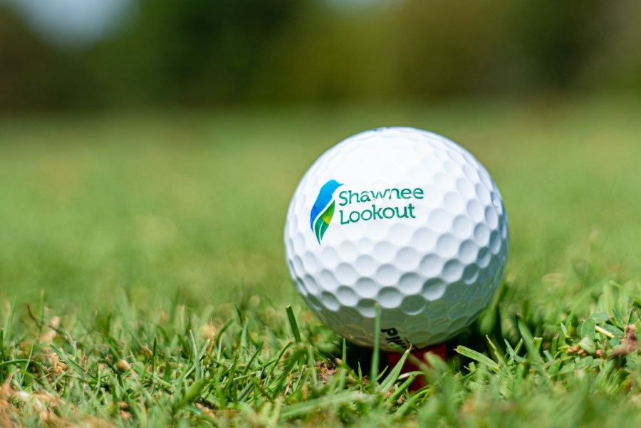 A golf ball with the Great Parks logo and the name Shawnee Lookout printed on it sits on the green.