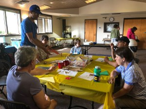 A group of adults participate in a craft during a sensory friendly hour at Miami Whitewater Forest Visitor Center.