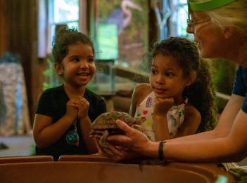 Nature interpreter Susan Sumner holds a turtle while two young park guests are excited to pet the turtle.