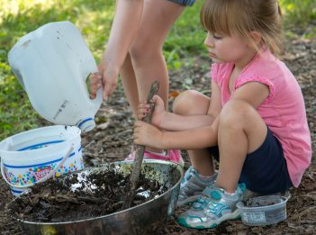 A young girl sits on the ground, mixing dirt and water together to create mud.