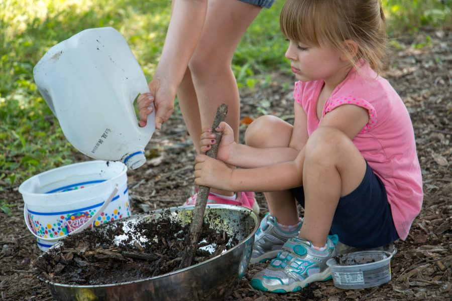 A young girl sits outside mixing together dirt and water to create mud.