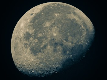 A nearly full moon shows craters and dark areas on its surface.