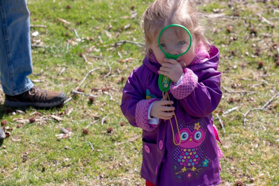 A young girl in a purple jacket holds a magnifying glass up to her eye. It is sunny.