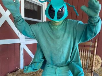 A man dressed in an emerald ash borer costume poses for the camera.