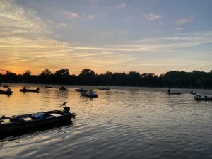 Anglers are in boats on Winton Lake at sunrise, heading out for a day of fishing.