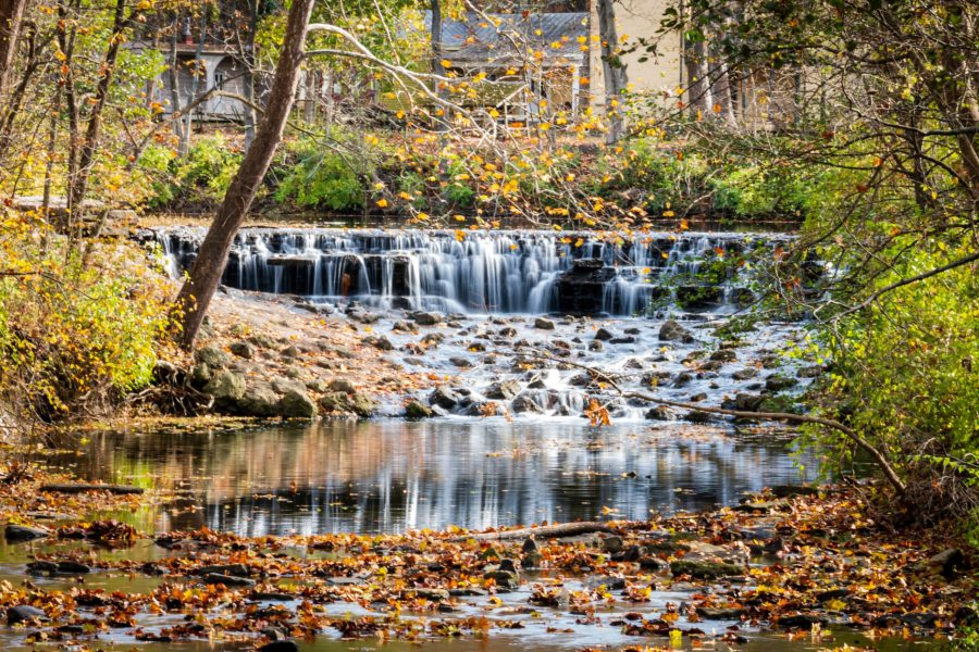 Buckeye Falls at Sharon Woods surrounded by red, orange and yellow falling leaves on a sunny autumn day.