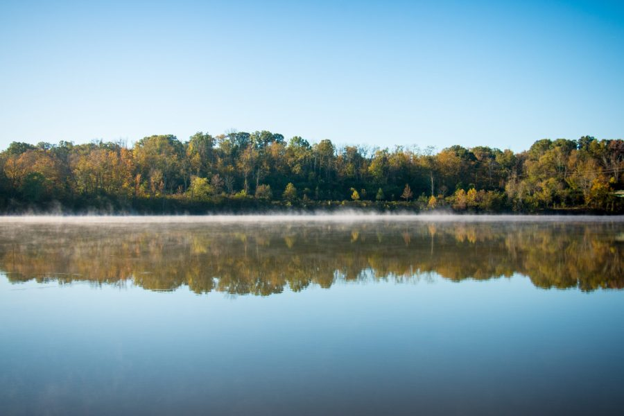 Trees show off their reflection in the water of Winton Lake on a sunny fall morning.