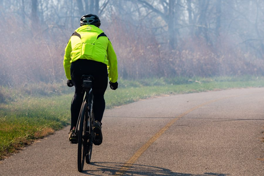 A person in a bright yellow jacket bikes on the paved trail at Miami Whitewater Forest.