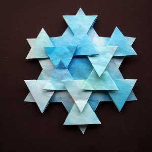 A snowflake made out of a coffee filter is dyed blue from food coloring.