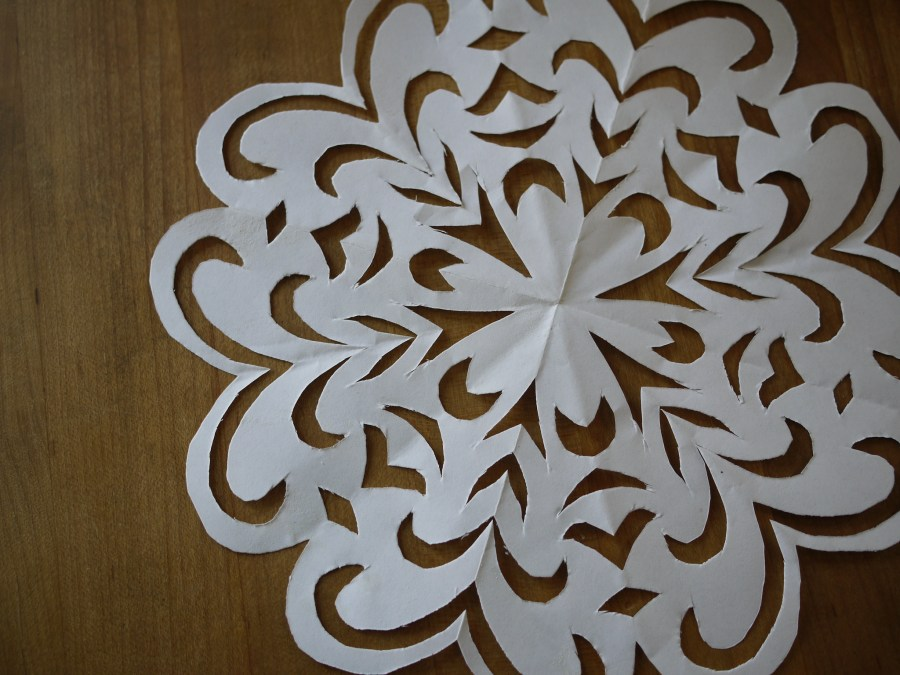 A snowflake made out of paper has swirling designs.