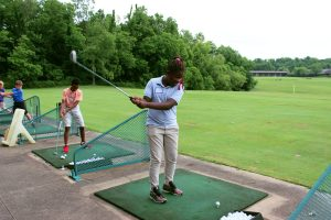 A girl is at the driving range, raising her club to hit a golf ball.
