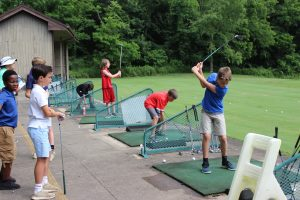 A group of children learn proper swing technique at the driving range.