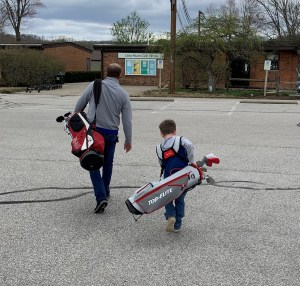 A father and son carry their clubs to the Little Miami Golf Center pro shop. The boy's golf clubs are as big as him.