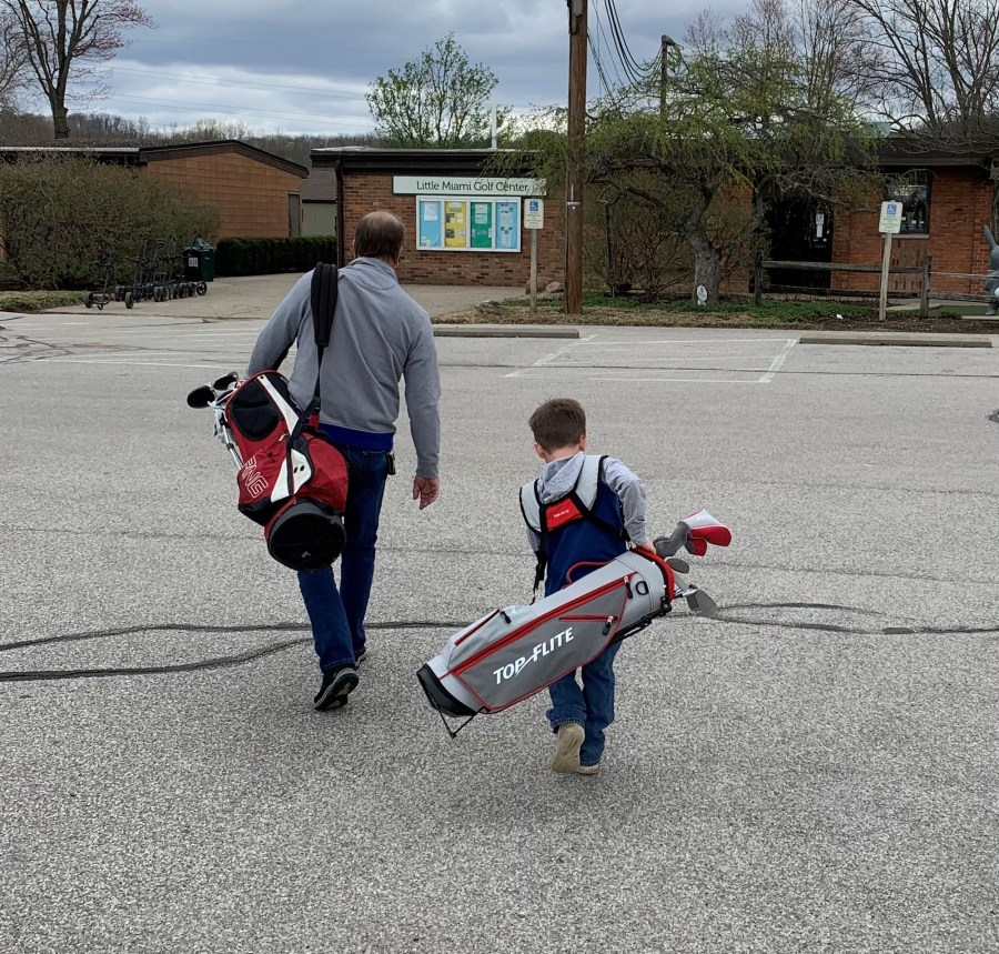 A father and son carry their clubs to the Little Miami Golf Center pro shop. The boy's golf clubs are as big as him!