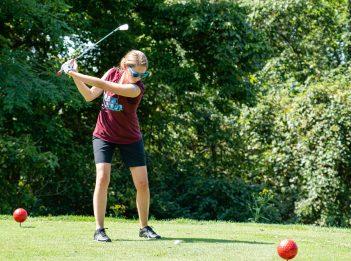 A woman raises her golf club, preparing to hit the ball.