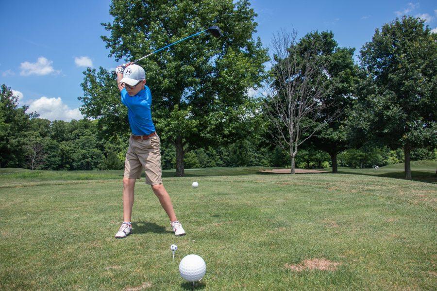 A young boy swings his club, preparing to hit golf ball.