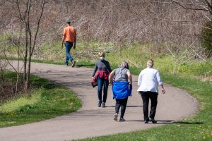 Several individuals walk along a paved trail on a sunny day.