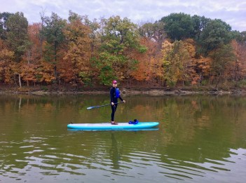 A woman stands on a stand-up paddleboard. She is in the middle of a lake.