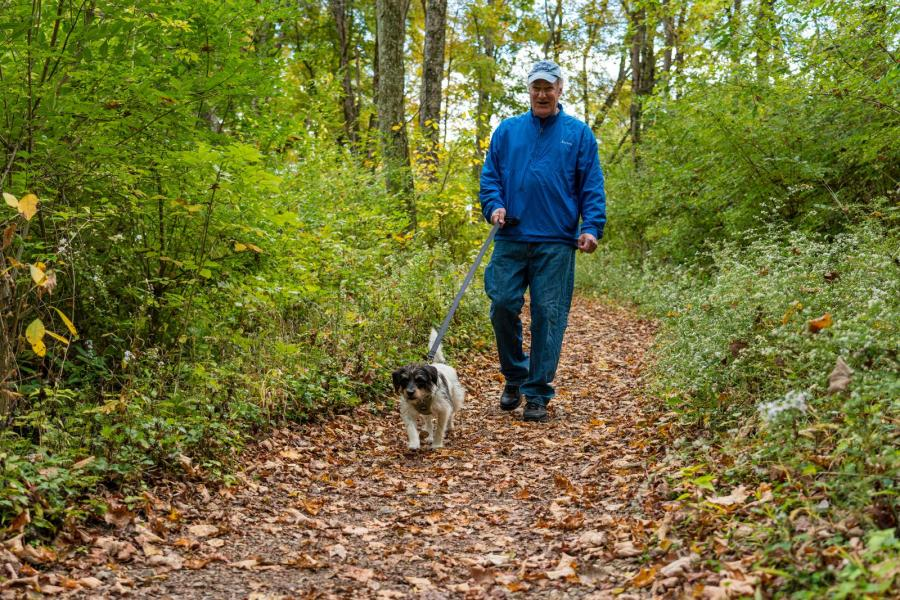 A man walks his dog on the Wood Duck Trail at Mitchell Memorial Forest.