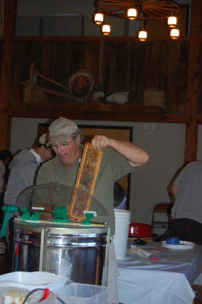 A man places honey frames inside a honey extractor.