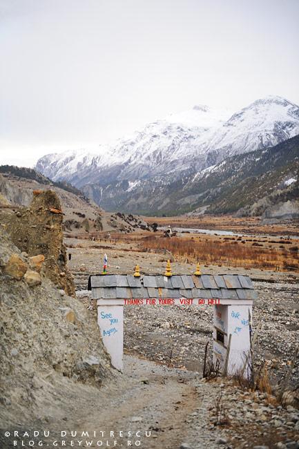 Imagine cu poarta budhistă de la intrarea în orașul Manang, cu un vârf de 6500m în fundal.