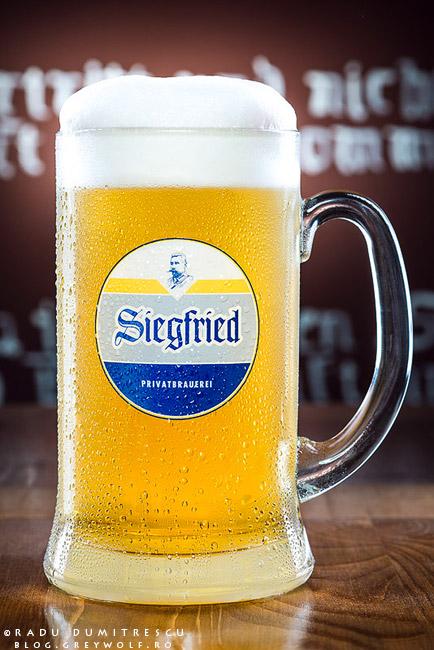 Fotografie de produs reprezentand o halba de 1 litru de bere blonda. Pe halba se pot vedea picaturi de apa, iar berea prezinta o spuma groasa, naturala.