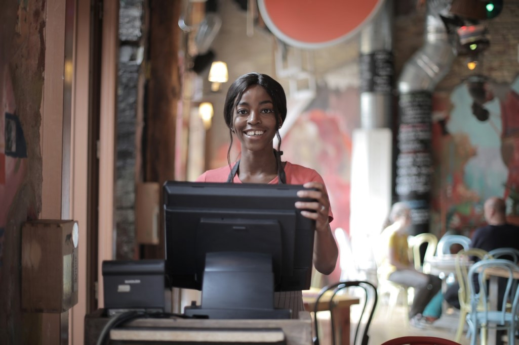 Smiling female restaurant employee behind register