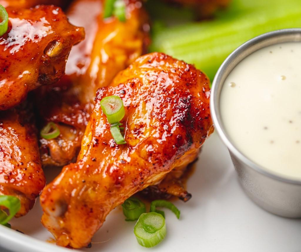 Juicy chicken wings beside dipping sauce at an Epic Wings N Things fundraiser