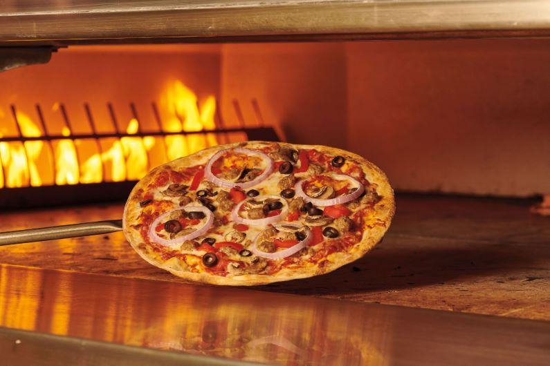 Large pizza on a paddle in a fire oven at a Best Buddies fundraiser