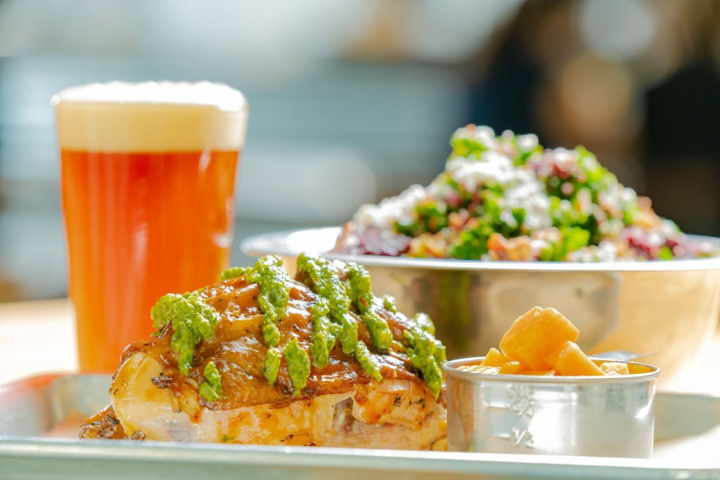Tasty chicken, tall beer, and large salad at Industry San Marcos