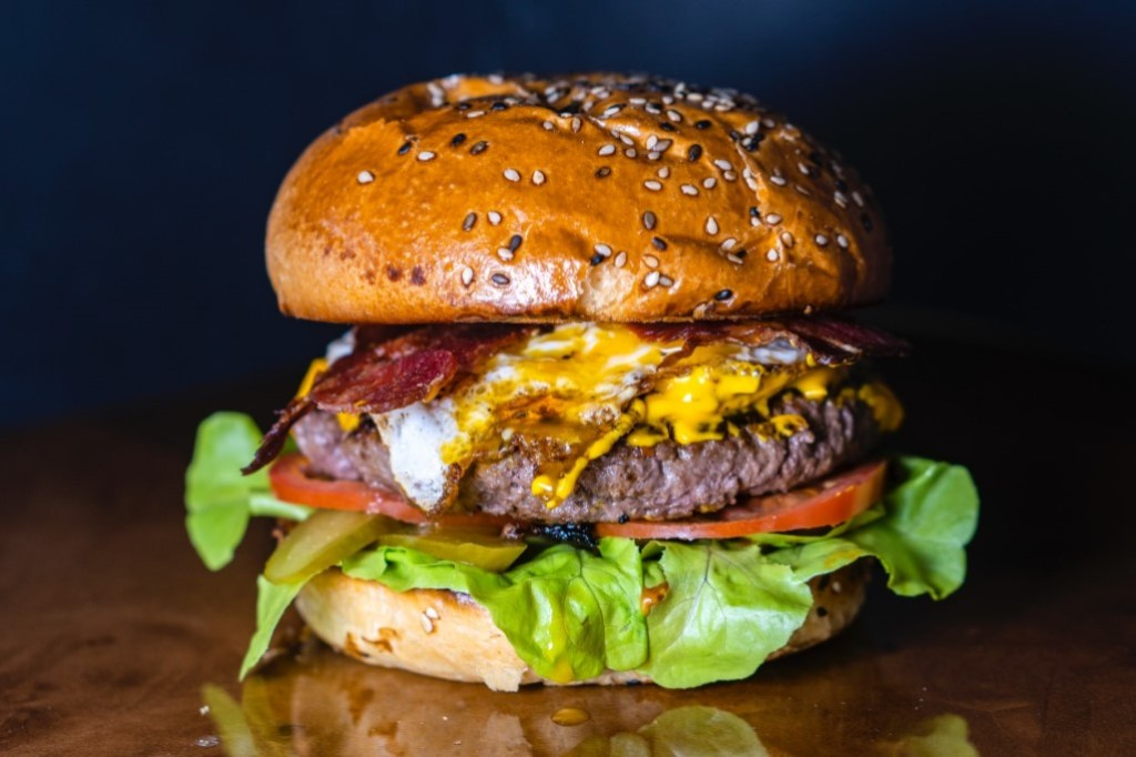 Large bacon cheeseburger with lettuce at a Farmer Boys fundraising event