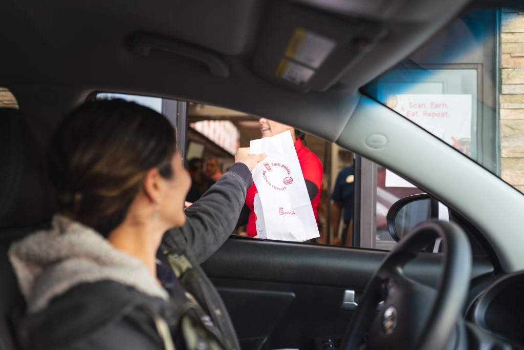Woman reaches from her car for her takeout order, a new way of coronavirus fundraising