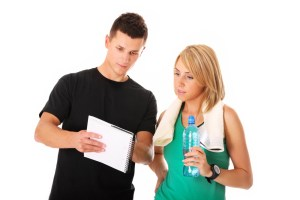 Personal trainer with clipboard talking to his client
