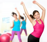 Energetic, happy fitness women dancing in a group class setting.
