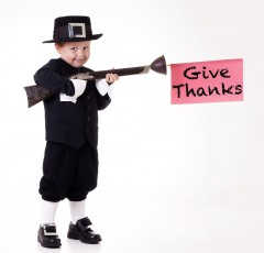 """Child dressed as a pilgrim with a sign that says """"give thanks"""""""