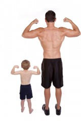 Father and son with backs to the camera flexing their biceps