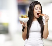Girl deciding to eat a slice of pizza instead of a salad bowl
