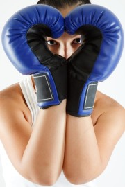 young woman in gym clothes, wearing blue boxing gloves shaped as a heart