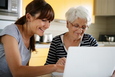 Musher qui aide un senior à surfer sur internet