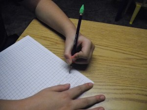 Graph paper provides visual cues for letter spacing and alignment.